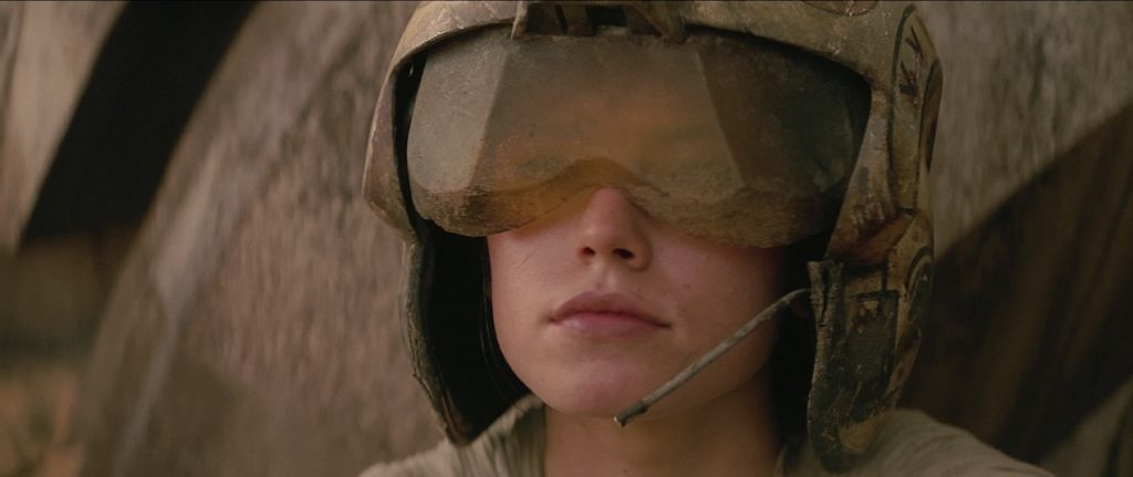 Rey wearing flight helmet hearing BB-8